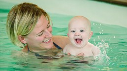 baby splashing in a pool with a mother for digital media and marketing