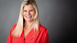 business headshot of a lady in a red top and black shirt